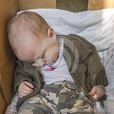 Small Baby sleeping in cardboard box.