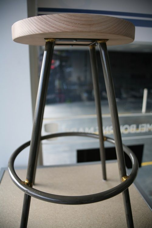 Industrial look round kitchen / bar / counter stool with timber top and clear powder-coated  base.