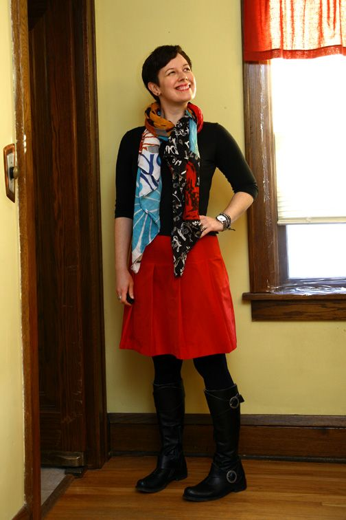 Bright patterned scarf, black top and tights, red skirt