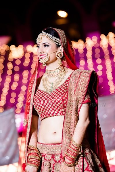 red and gold lehenga, gold bridal jewelry, gold pearls mathapatti, red bangles , banarsi blouse , red
