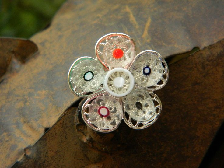 A unique and quirky brooch.   Millefiori cut glass on a silver metal alloy flower shaped base. Width 2.5 cm, depth 1 cm.    https://www.madeit.com.au/Main/Item?itemId=956786