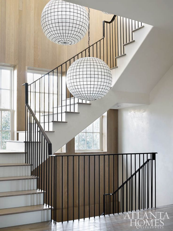 Spherical glass lighting from Restoration Hardware creates a striking focal point on the staircase.