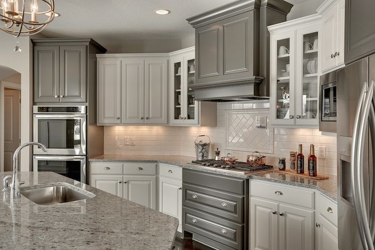 Beautiful kitchen features dark gray cabinets painted Benjamin Moore Kendall Charcoal alongside white cabinetry united by brushed nickel hardware and Moon White Granite counters alongside a simple white subway tiled backsplash.