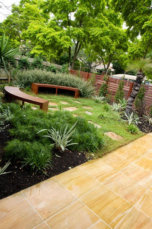 Groundcovers, grasses, and stepping stones sub in for a front lawn