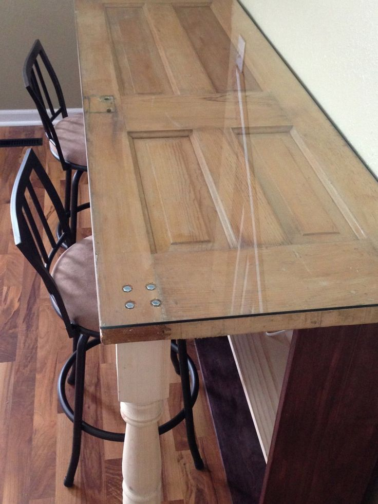 This handy father recycled an old door into a new desk. The desk has shelving storage underneath with banister front legs and a glass top.