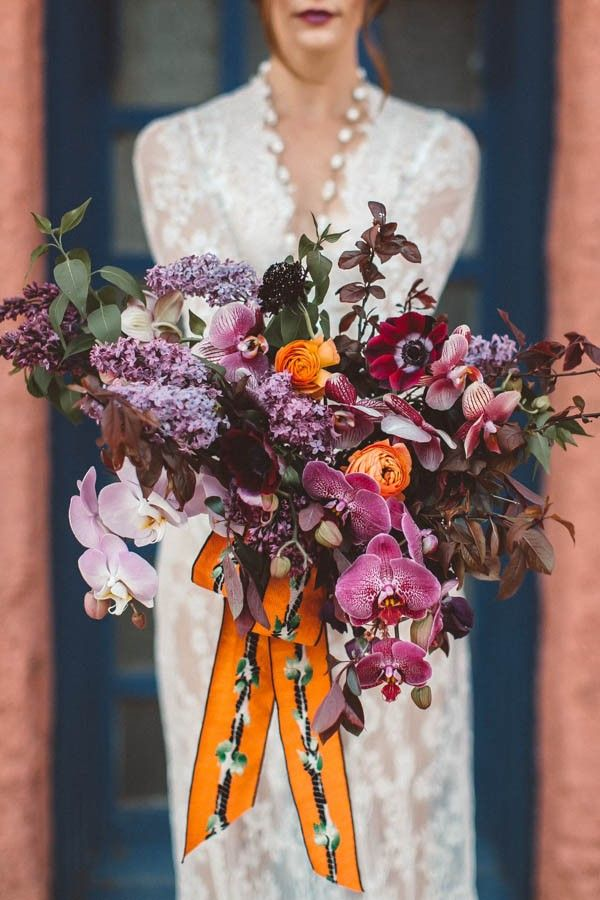 Stunning purple wedding bouquet with an unexpected pop of orange | Image by Alicia Lucia Photography