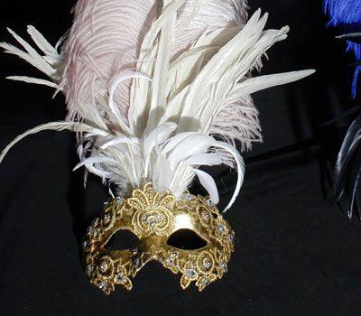 Maschra con piume bianche e decorata con macramè color oro SA48. Maschera originale veneziana realizzata a mano in cartapesta. Decorata con foglia d'oro, tecnica dello screpolato, pizzo macramè ed impreziosita da cristalli Swarovski e perle.