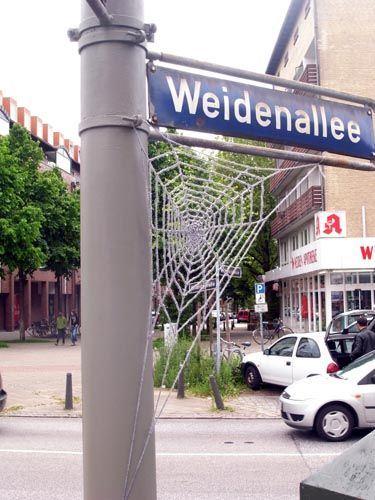 Guerilla Knitting - Knitted Spiderweb on Street Sign yarn bomb