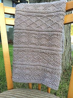 A beautiful, unisex baby blanket in Guernsey, or Gansey, patterns. This classic blanket knits up fast in a bulky weight yarn, and the knit/purl pattern provides great texture. The yarn is also machine washable to make things easier for new moms.