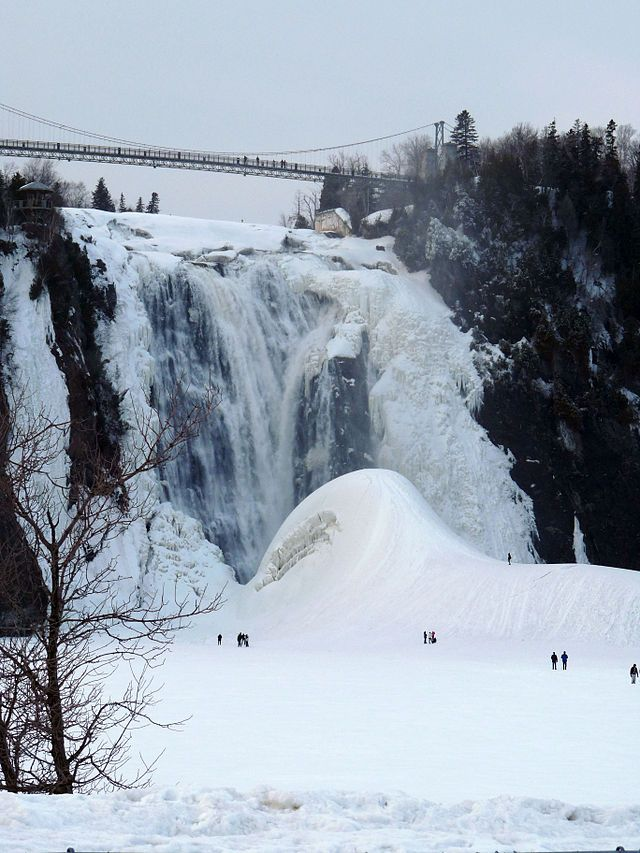 RN - La Chute Montmorency se situe à quelques mètres du fleuve Saint-Laurent, à l'embouchure de la Rivière Montmorency. Le «Pain de sucre» se forme au pied de la chute en hiver, après le gel de la rivière, quand les embruns produits par la chute gèlent sur la couche de glace.