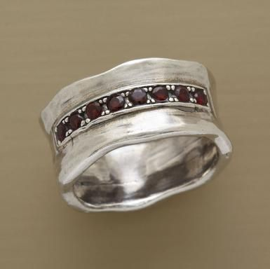 """An arc of garnets, a gem said to inspire courage, caps our hefty sterling silver ring. A hand cast Sundance exclusive in whole sizes 5 to 9. Approx. 3/8""""W."""