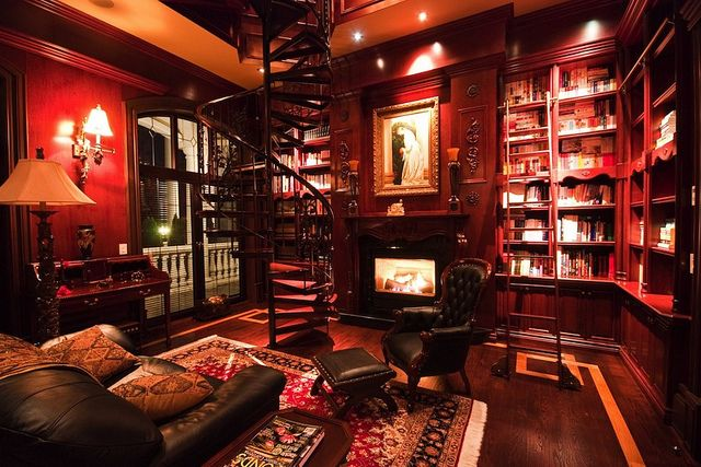 Old mansion interior home library. This has everything I could ever want in a library. Books. Fireplace. Circular Stars. Ladder to get to high shelves. Comfy chairs. ..I could LIVE in here. <3
