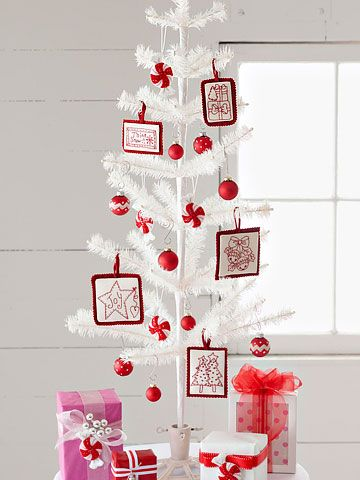 plain white tinsel or feather tree with mix of bold red ornaments and embroidered patterns. placed on table w grouping of bright presents