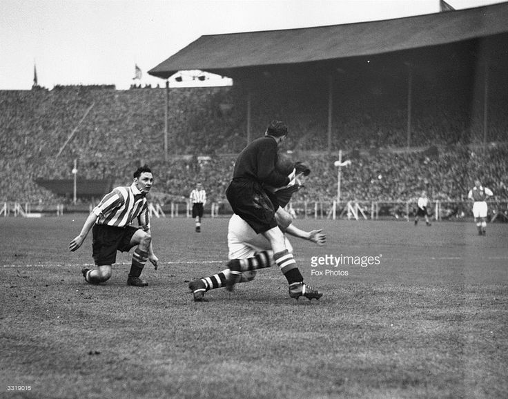 Sheffield United goalkeeper Smith saves the ball as Arsenal's Ted Drake charges him during the FA Cup Final at Wembley Stadium. The final score was Arsenal 1-0 Sheffield United.
