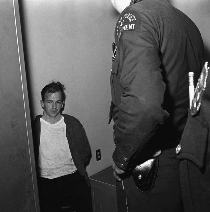 JFK's last day - The assassination of an American President - Lee Harvey Oswald sits in police custody shortly after being arrested for assassinating U.S. President John F. Kennedy in Dallas, TX, Nov. 22, 1962.  Oswald was shot and killed two days later by Jack Ruby, a local club owner as he was being transferred to a city jail.  (AP Photo)