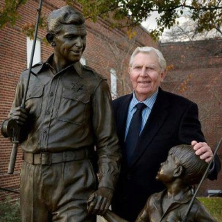 Andy Griffith standing next to the statue in Mount Airy, NC, that honors The Andy Griffith Show.