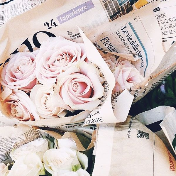 Newspaper wrapped roses. Beautiful. Although I'm sure the fact they're not in English helps with the romance.