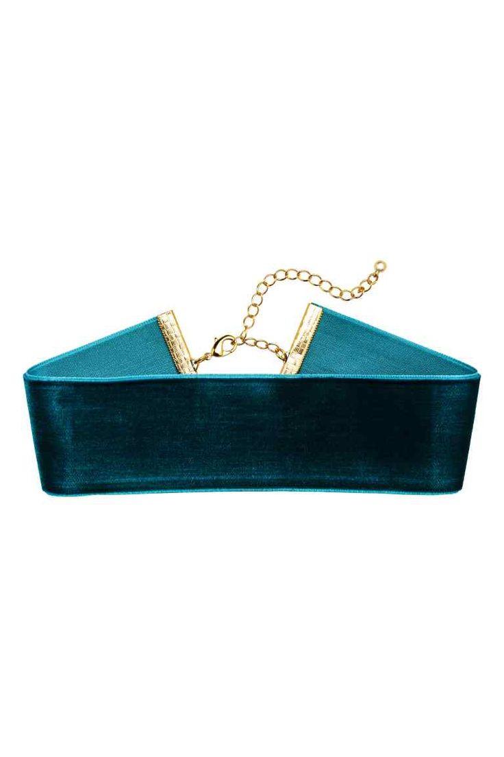 Ras-de-cou en velours: Collier court constitué d'un ruban en velours avec finition et fermoir en métal. Longueur réglable, 30-37 cm.