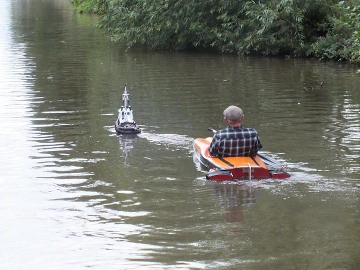 """Last Monday, as he passed through the north England town of Market Drayton, Mick Carrollsaw something unusual coming towards him. An older gent was merrily cruising down the canal with the help of a small remote-controlled tug boat. Carroll snapped a few photographs and posted on Facebook: """"Dont ya just love eccentric's. Seen this fella as we were passin thru Market Drayton gettin pulled along by a remote control tug. Brilliant."""" According to Carroll's post, the man shouted to Carroll…"""