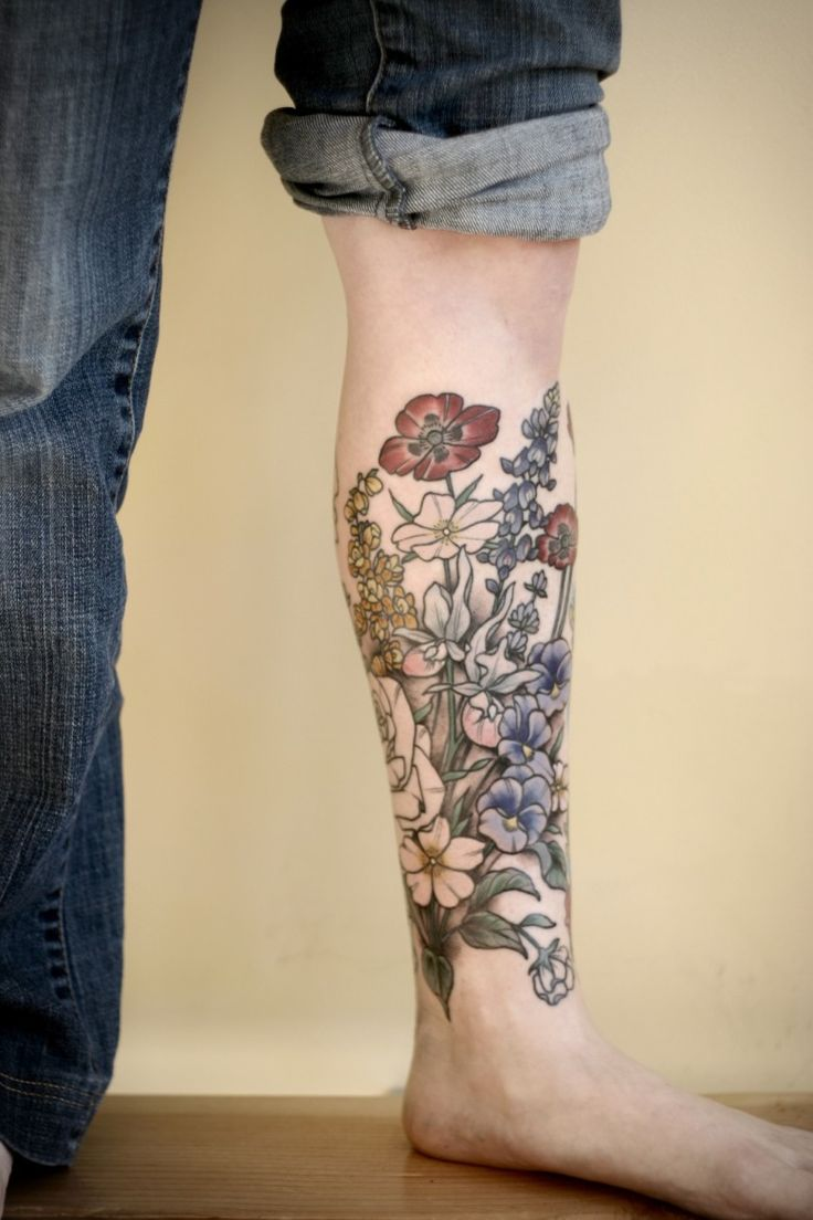 Fabulous floral shin tattoo. It has a stunning variety of colors and different flower types which covers the shin all around.