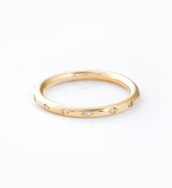 """Round details abound in this understated diamond band. Rather than covering every surface in gems, designer Brooke Miller opts for a """"less is more"""" approach, putting a bit of space between each diamond and flanking them with tiny solid gold beads, all on a rounded band. Put all these elements together and you have a simple statement that's minimal and modern, but with a perfect feminine flair. Wear it as an everyday fashion piece or pair it with your engagement ring for a streamlined band…"""