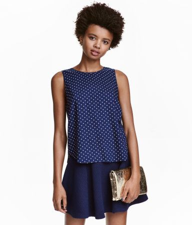 Dark blue. Sleeveless blouse in woven fabric with a printed pattern. Buttons at back and a rounded hem.