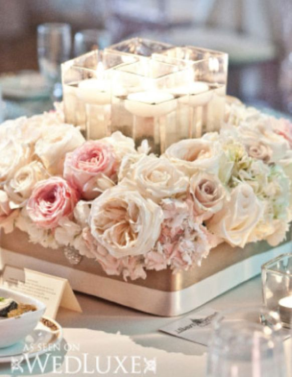 Pink and white wedding flower centrepiece with candles