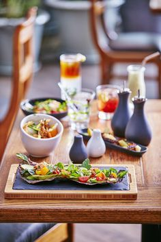 Une jolie table haute en couleurs!  La planche Basalte sur plateau en bois souligne les couleurs fraîches des aliments.  Elle est accompagnée par le bol Basalte, la salière et la poivrière Likid et l'huilier et le vinaigrier Likid.  Ces vaisselle artisanale produits en céramique par Revol, avec le plateau, le bol oblique et cruets de conception sont si élégant dans la table.
