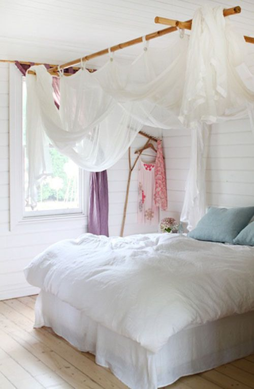 Bamboo Rod Suspended From Ceiling Over Bed For Mosquito Net.