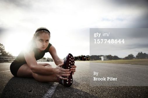 fitness modeling photo shoot ideas - Young woman athlete stretching on track