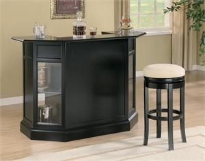 Bar Unit Item #100175-A contemporary black bar with a serving area in the shape of half an octagon. Bar features wine bottle holders and shelving with a hanging stemware rack above.