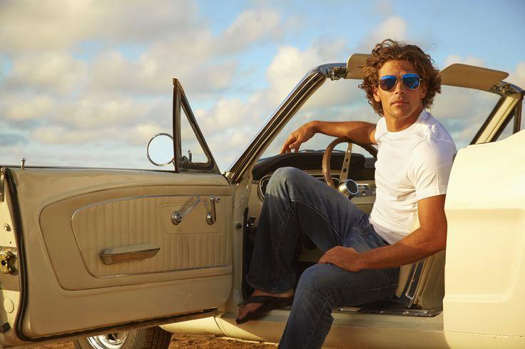 Caucasian man relaxing in convertible on beach - Caucasian man relaxing in…
