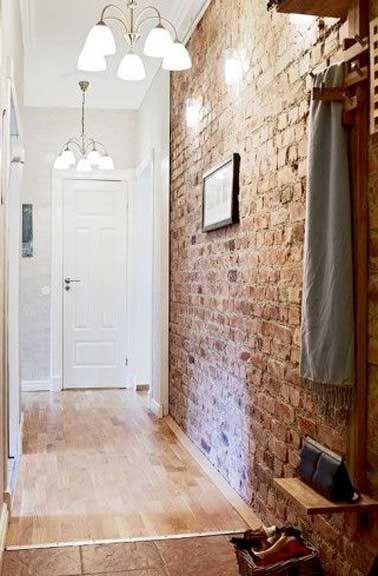 Un mur de briques rouge fait la déco du couloir