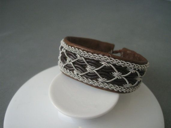 Traditional wide Sami bracelet made of a reindeer leather. The ornament is made of reindeer leather cord and pewter wire. The bracelet closes with a button made of reindeer antler. The bracelet is 18.5 cm (7-1/4) long from end to end. The bracelet is 2.2 cm (7/8) wide. Elegant vintage handmade item, excellent condition.