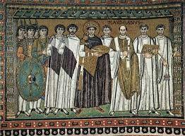 """""""Mosaico de Justiniano y su corte"""". Se encuentra en la Iglesia de San Vital de Rávena, Italia. Es un mosaico del siglo VI. Está hecho de terselas de cerámica, marfíl, oro, hueso y piedras preciosas. Se encuentran los guerreros, Narses y Belisario, Justiniano, el banquero que costeó la iglesia, Maximiliano (obispo de Rávena) y otros miembros de la iglesia."""