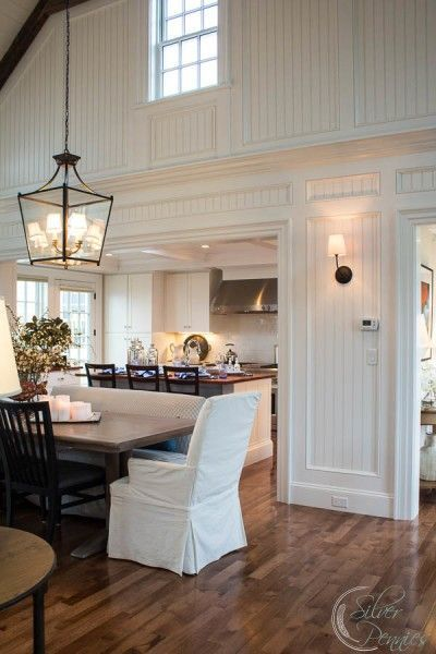 Fabulous white country kitchen   clerestory window   beadboard   beautiful mouldings   cool lantern over the table   slip covered dining chair   wall sconces   mismatched chairs