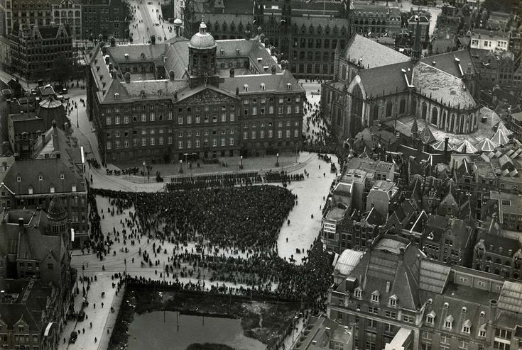 Gezicht vanaf hoog standpunt van de Dam in Amsterdam tijdens het bezoek van koning Haakon VII van Noorwegen aan deze stad samen met Koningin Wilhelmina. Het Paleis op de Dam en de Nieuwe Kerk zijn duidelijk zichtbaar. In het midden ziet het zwart van de mensen. Nederland, 1923.