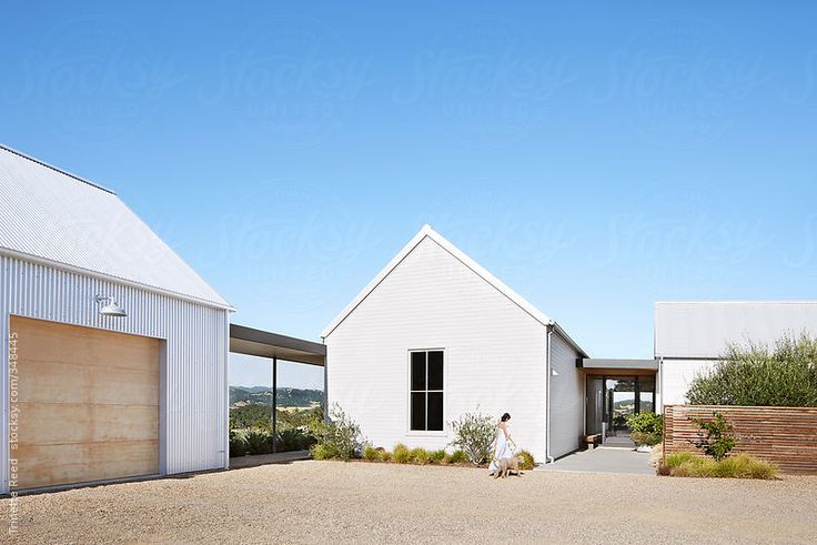 Woman and her dog walking in front of modern farmhouse by Trinette Reed for Stocksy United