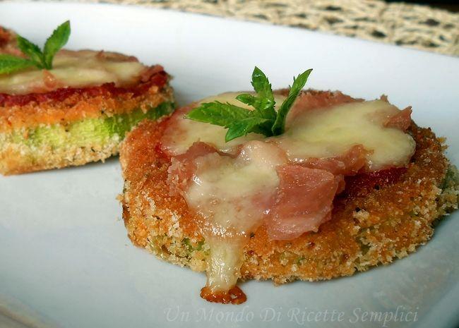 Le zucchine alla pizzaiola sono rondelle di zucchine cosparse con del sugo di pomodoro,del prosciutto,un po' di mozzarella e cotte in forno.Golosissime!!