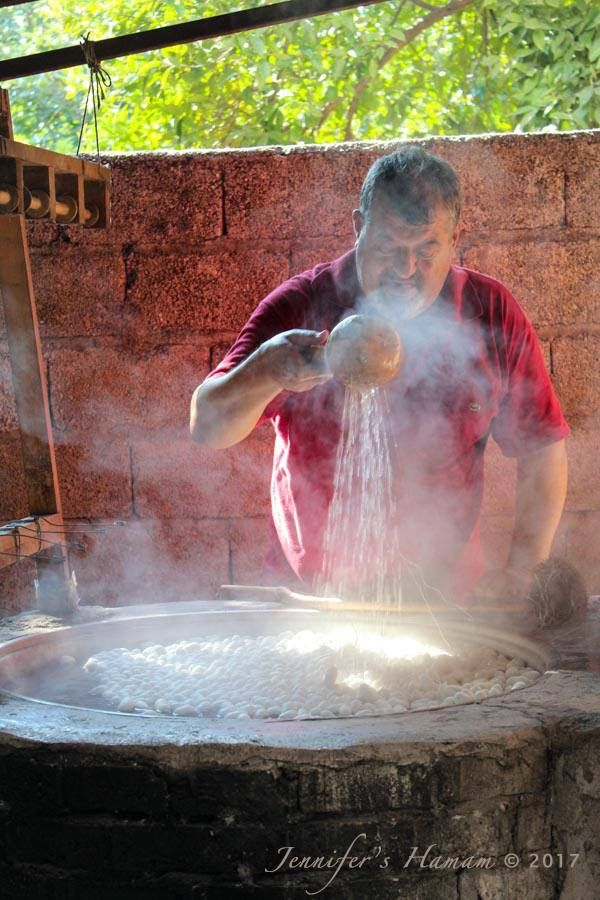 Cocoons are in the hot water; the artisan reeler adds cold water to get the temperature just right before he starts reeling the silk to ensure the strongest silk threads possible.   #reelingsilk #silk #cocoon #jennifershamam #silkworms #silkscarf #artisan #weaving