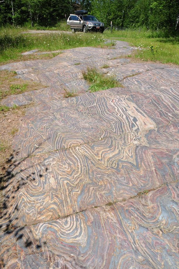 Folded banded iron formation with shale interbeds, exposed in a pavement near Soudan, Minnesota.
