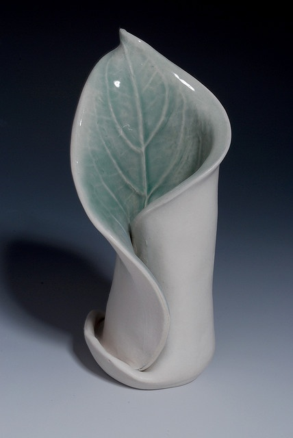 A simple slab technique creating a vase from one piece of clay with a leaf impression on it.
