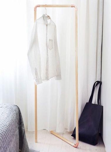 Pour obtenir un espace penderie supplémentaire dans la chambre, voici un portant vêtement très facile à réaliser avec des barres en bois et des coudes en cuivre