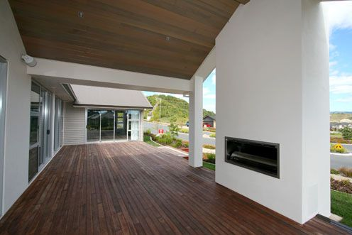 An outdoor fireplace with covered decking. The media room sits at the far end of the deck.