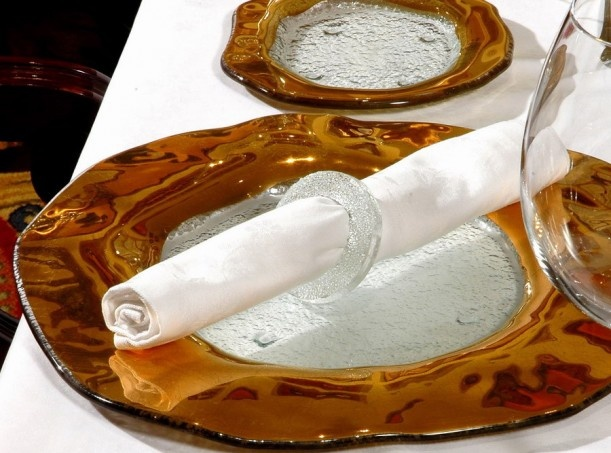 Gold dinnerware set with gold-rim glass charger plate and side plate and glass napkin ring. For luxurious dining setup. By Glass Studio