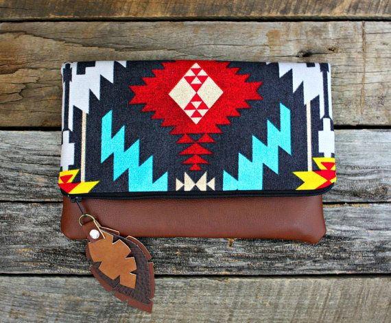 Made to order. Ships out 2 to 4 days after purchase.  This foldover clutch has an eye-catching Aztec Navajo fabric. Accented with faux leather feathers attached to the zipper. It has a copper brown faux leather bottom. Natural canvas fabric on the inside with 2 pockets.  This is the perfect size to carry your items in: your cell phone, keys, make-up, money, small camera, wallet. Dont want to carry a big bulky purse? This is the perfect size to grab and go for a day out shopping…