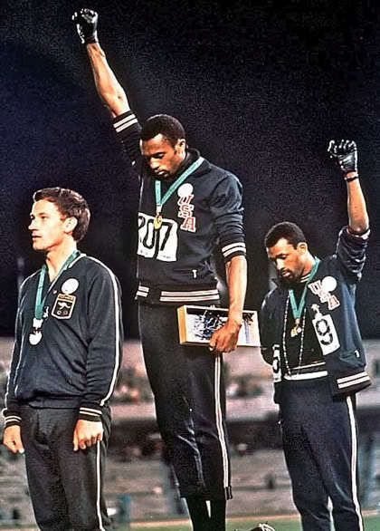 """Fists of Freedom: An Olympic Story Not Taught in Schools"" (GOOD Magazine) -- on media misrepresentation of a historic moment; alternate textbook captions include (1) ""Young Leaders Call for Black Power"" vs. (2) ""...U.S. athletes Tommie Smith and John Carlos raised gloved fists in protest against discrimination."""