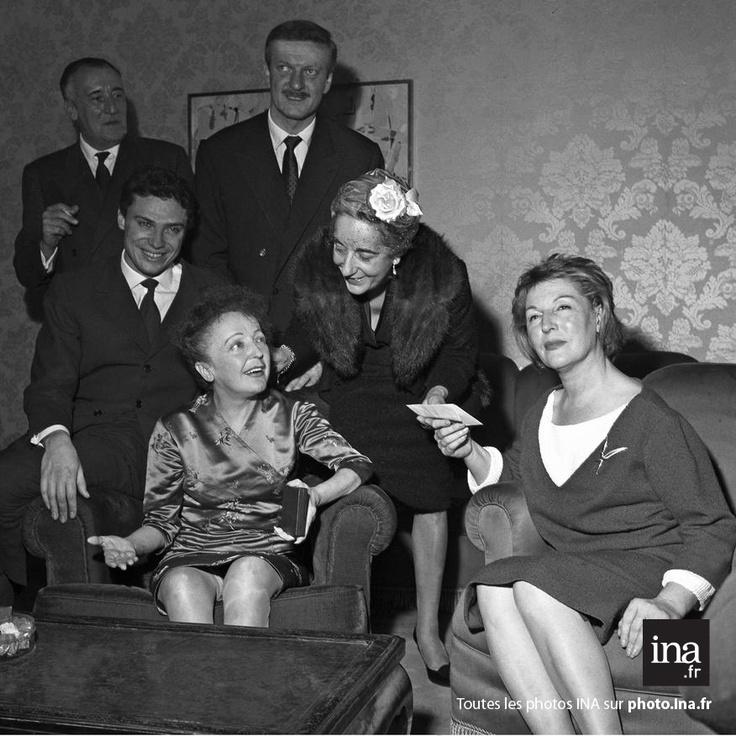"""Edith Piaf, entourée de Paul Gilson, Georges Moustaki, Hubert Ithier et Marguerite Monnot, vient de recevoir le blason d'or du marathon de la chanson française pour sa chanson """"Milord"""", 1960"""