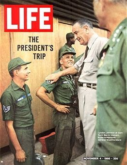 The cover of Life magazine features a photograph of American President Lyndon Baines Johnson (1908 - 1973) (center) as he talks with American airman at Cam Ranh Bay Air Base, Cam Ranh Bay, Vietnam, November 4, 1966. One of the airman is named Minucci, and standing at extreme right, mostly out of frame, is American General William Westmoreland (1914 - 2005).