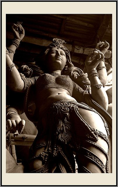 "Goddess Durga - photo by Soumya. Sanskrit: ""the inaccessible"", Bengali: দুর্গা) is a form of Devi, the supreme goddess. In Bengal, she is said to be the mother of Ganesha, Kartikeya as well of Saraswati and Lakshmi. Durga is depicted as a warrior woman riding a lion or a tiger with multiple hands carrying weapons and assuming mudras, or symbolic hand gestures. This form of the Goddess is the embodiment of feminine and creative energy (Shakti)."
